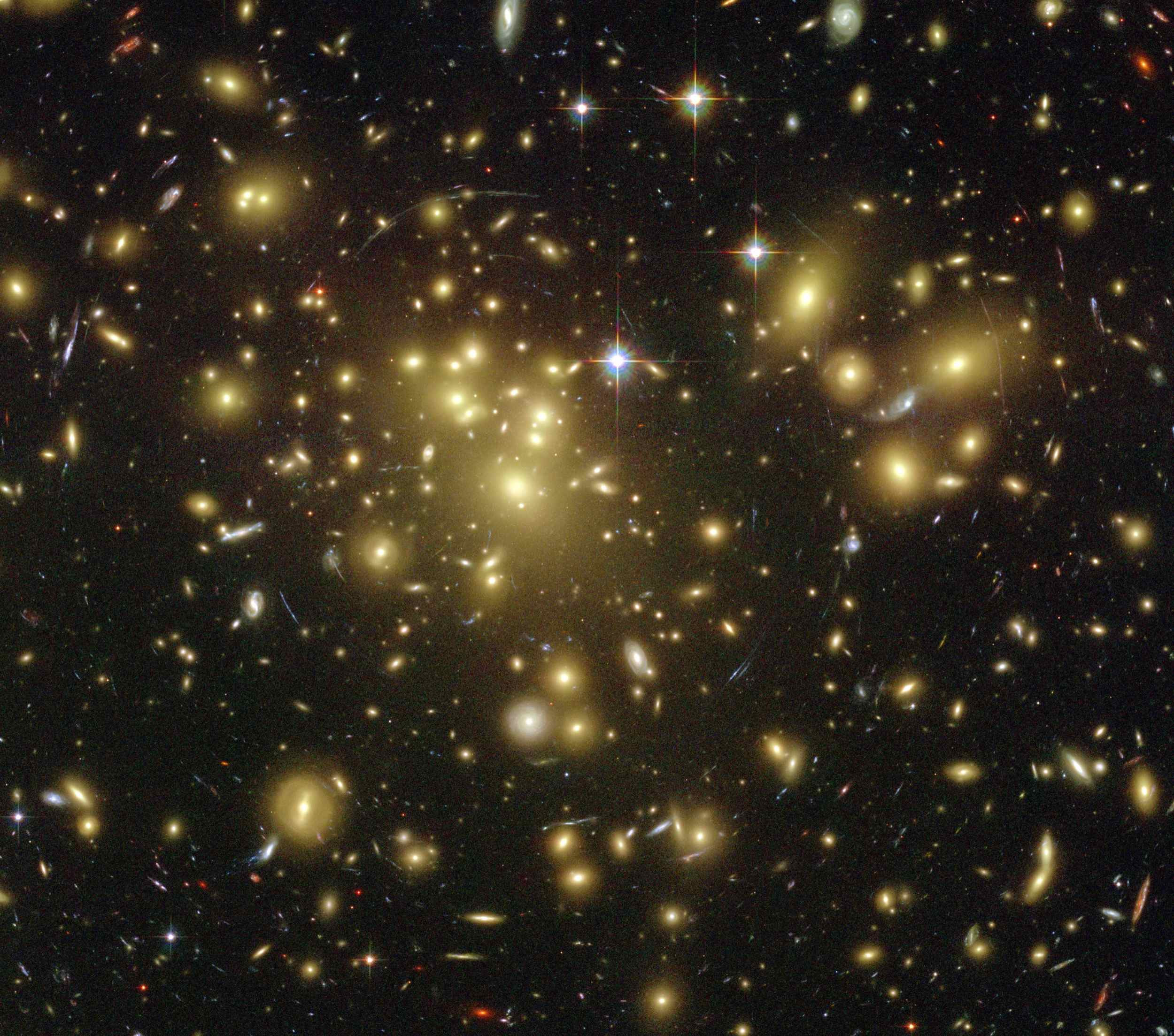 A massive cluster of yellowish galaxies is seemingly caught in a spider web of eerily distorted background galaxies in the left-hand image, taken with the Advanced Camera for Surveys (ACS) aboard NASA's Hubble Space Telescope.