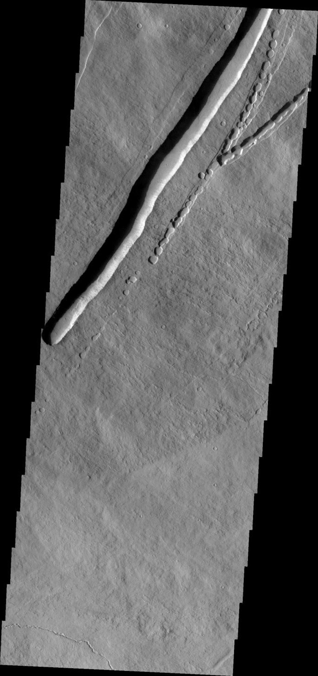 This image from NASA's Mars Odyssey shows the eastern flank of Pavonis Mons on Mars with a large collapse feature and the initiation of a similar feature with small collapses to the east.