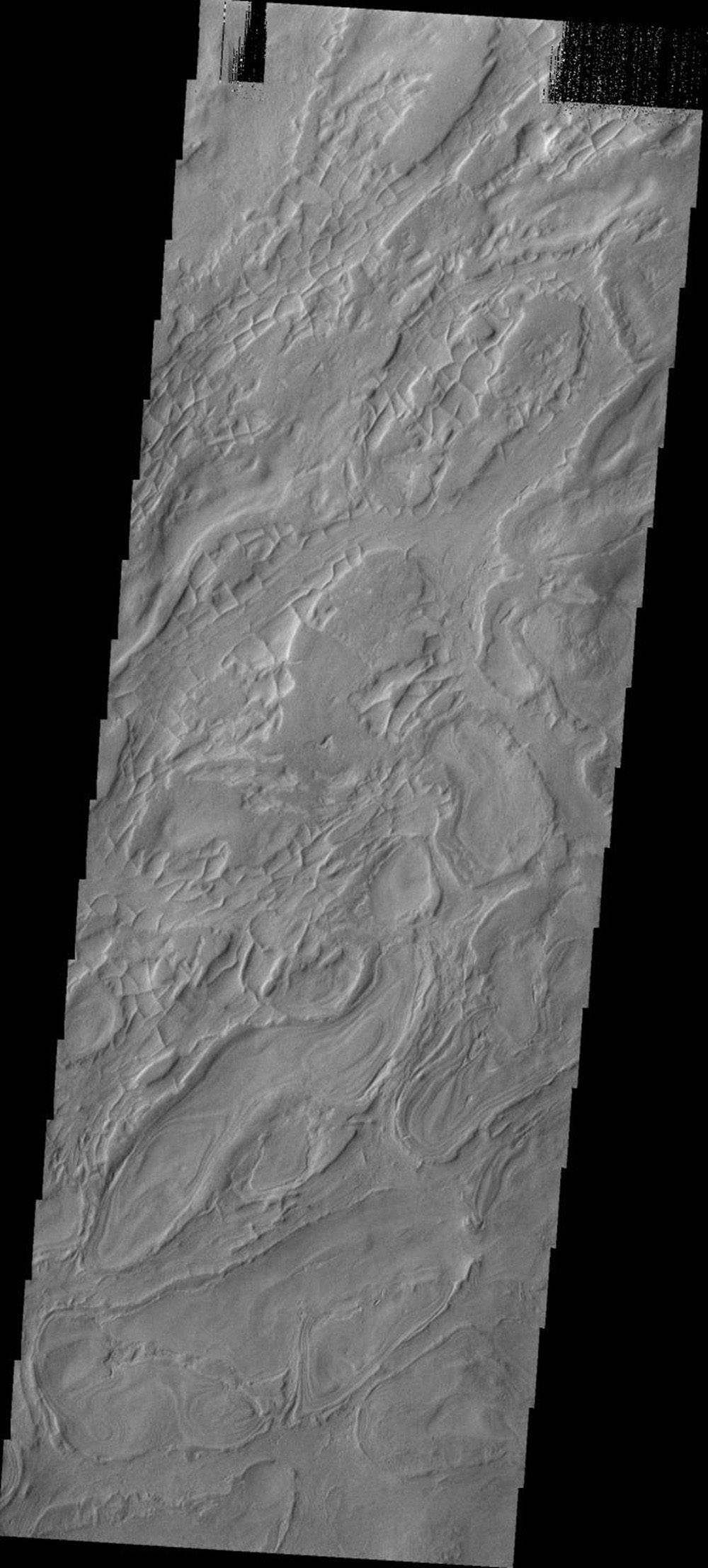 This image from NASA's Mars Odyssey shows a small portion of the western floor of Hellas Basin on Mars. The curved, broad ridges are separated by lower elevations filled with smaller, linear ridges.
