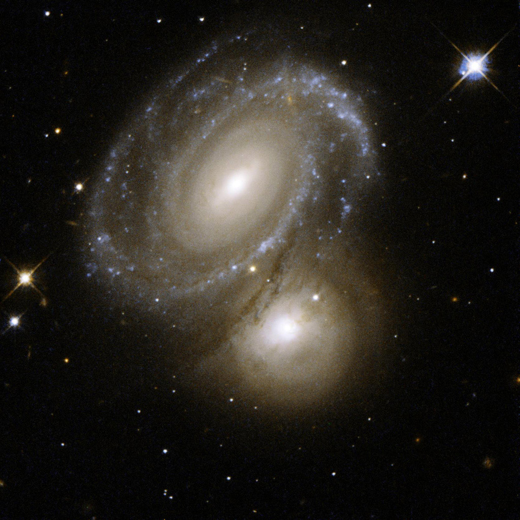 AM 0500-620 consists of a highly symmetric spiral galaxy seen nearly face-on and partially backlit by a background galaxy. This image is part of a large collection of images of merging galaxies taken by NASA's Hubble Space Telescope.