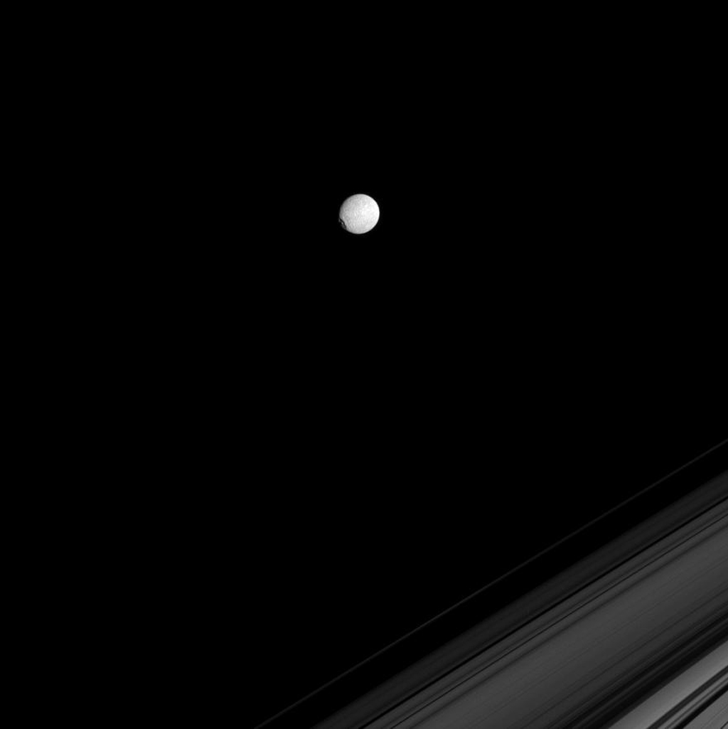 NASA's Cassini spacecraft spies Saturn's icy moon Mimas on the far side of Saturn's rings. The large crater Herschel gives the moon a flattened profile on its leading hemisphere, at left.
