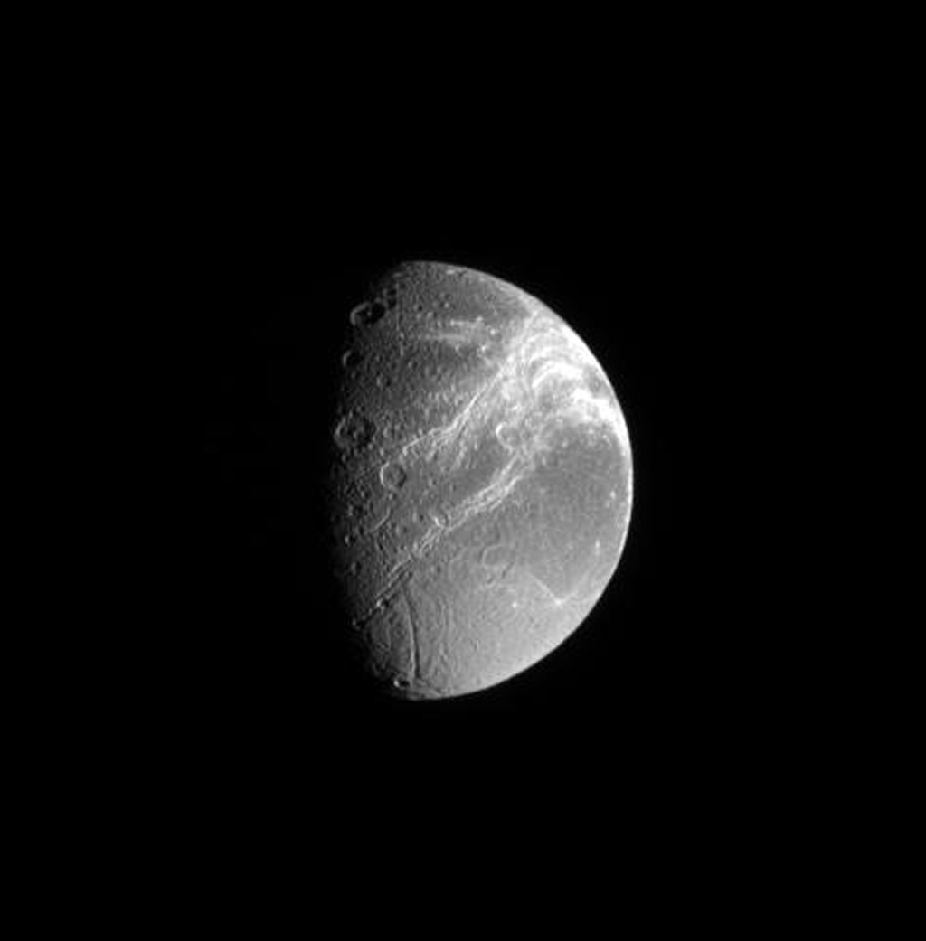 Saturn's moon Dione's defining feature, the fractures on its trailing side, shine brilliantly in this image captured by NASA's Cassini spacecraft.