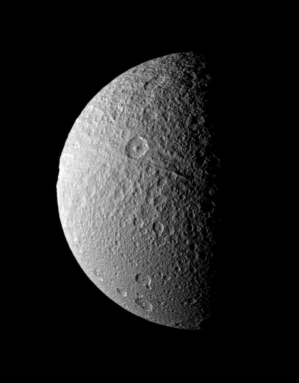 Ithaca Chasma, an enormous rift that stretches from north to south across the face of Tethys, seemingly takes a bite out of the moon's limb in this image from NASA's Cassini spacecraft taken on Dec. 9, 2008.