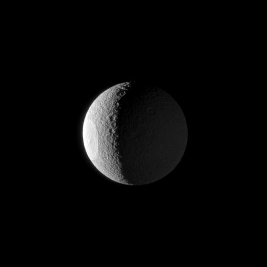The huge Odysseus Crater is clearly illuminated by the sun on the western limb of Tethys, with Saturn shining from the right in this image from NASA's Cassini spacecraft taken on Jan. 22, 2009.