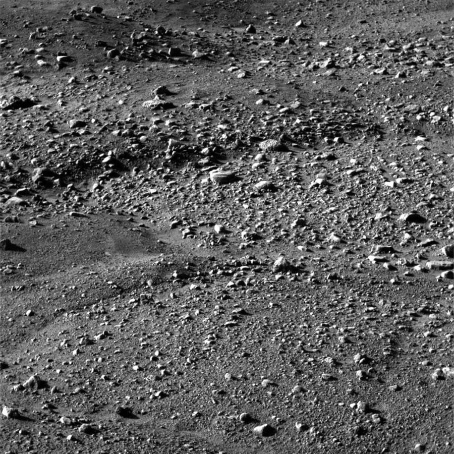 NASA's Phoenix Mars Lander shows flat ground strewn with tiny pebbles and marked by small-scale polygonal cracking, a pattern seen widely in Martian high latitudes.