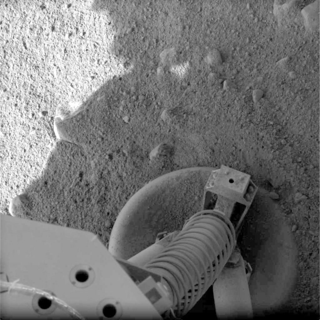 This view of a portion of the spacecraft deck and one of the footpads of NASA's three-legged Phoenix Mars Lander shows a solid surface at the spacecraft's landing site.