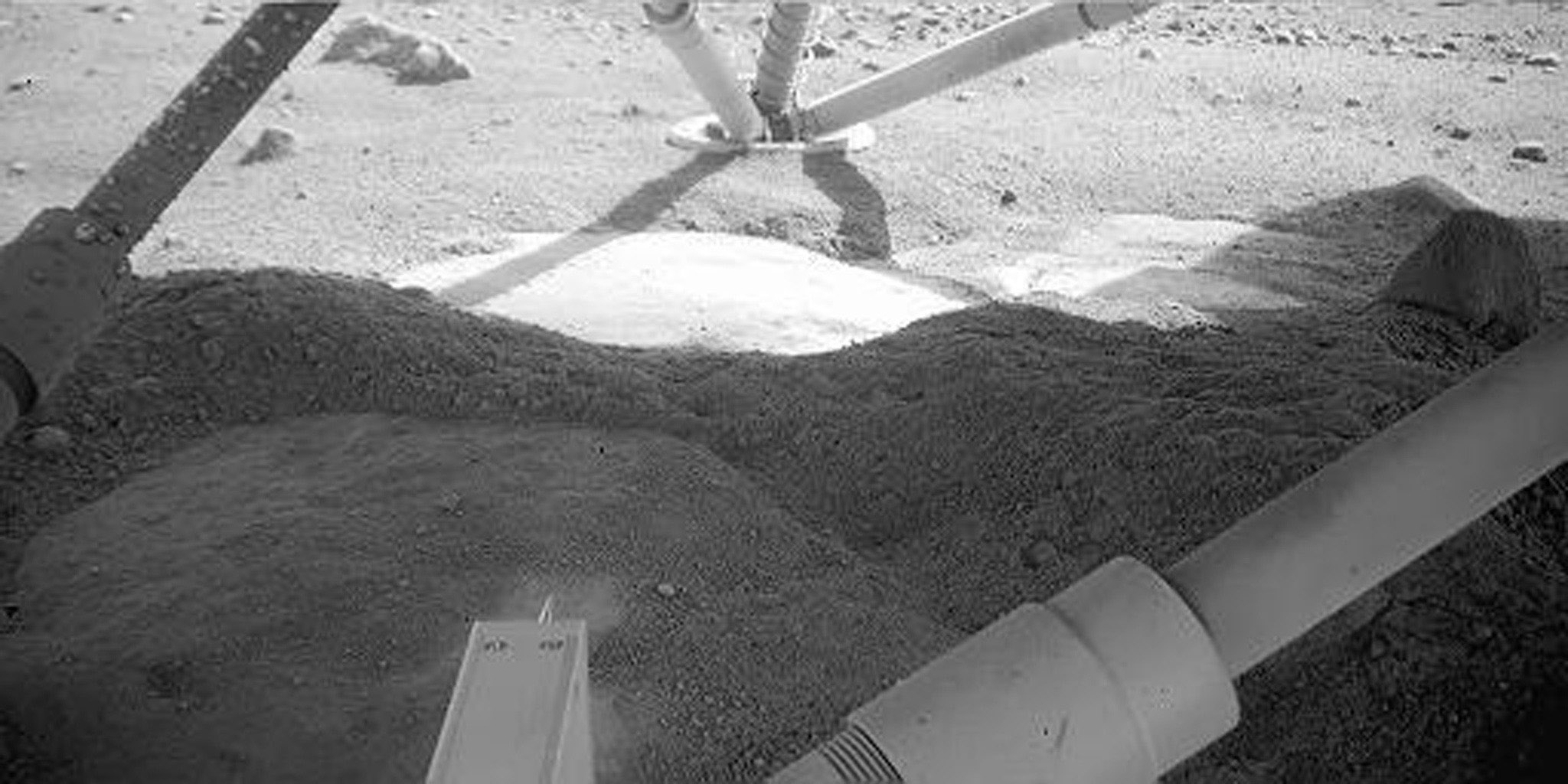 NASA's Phoenix Mars Lander shows the martian surface beneath it. The light feature below the leg is informally called 'Holy Cow.'