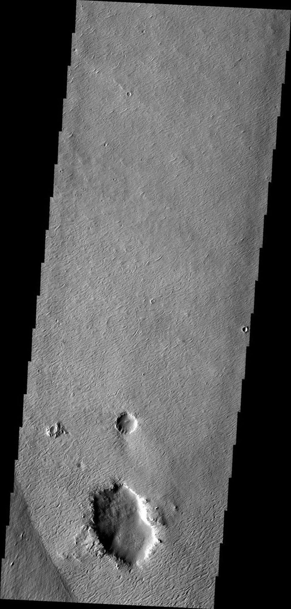 This image from NASA's Mars Odyssey shows wind, craters, and an easily eroded material have combined to produce this interesting region of features on Mars.