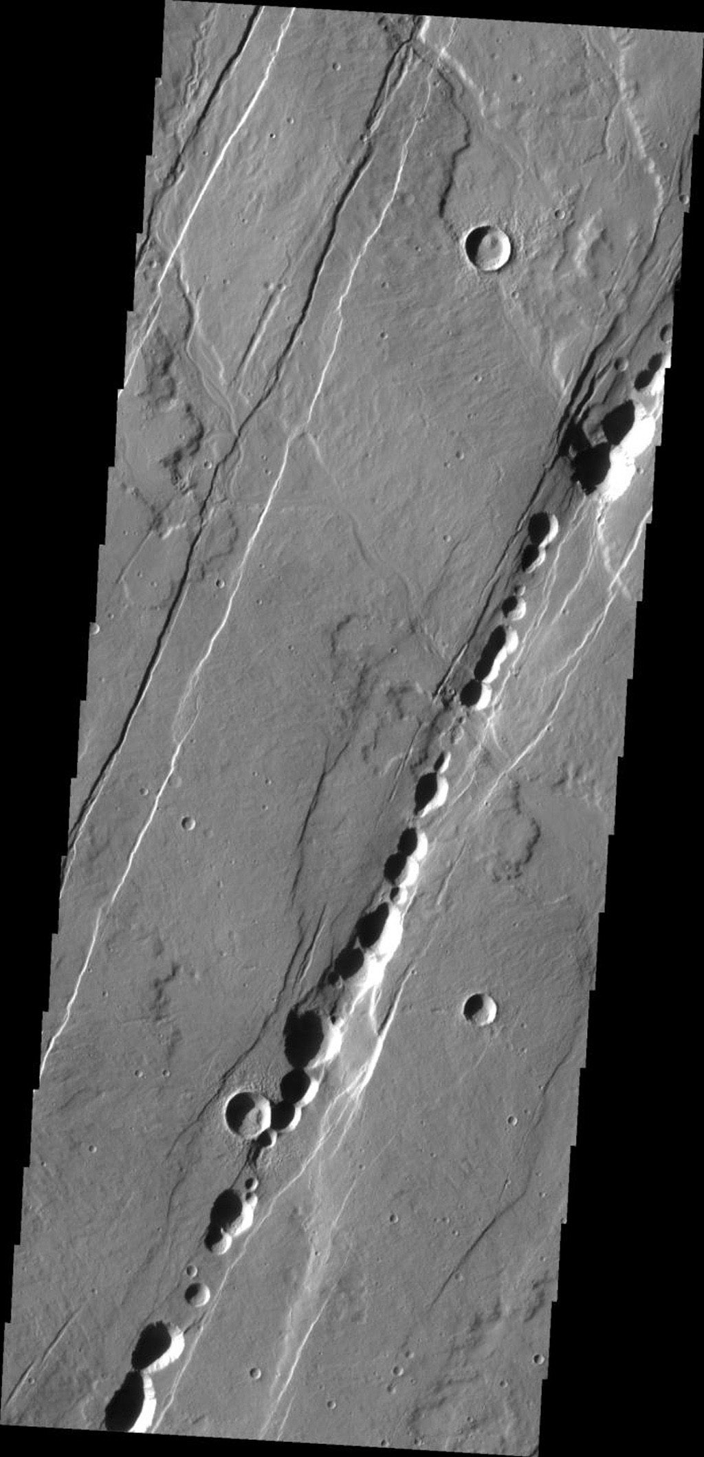 This image from NASA's Mars Odyssey shows the ancient collapsed volcano, Alba Patera, surrounded by graben and collapse features termed catenae on Mars.