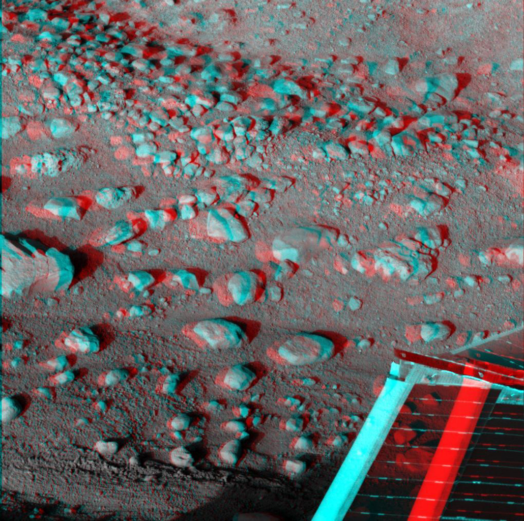 This anaglyph, acquired by NASA's Phoenix Lander's show Phoenix's solar panel is seen in the bottom right corner of the image. 3D glasses are necessary to view this image.