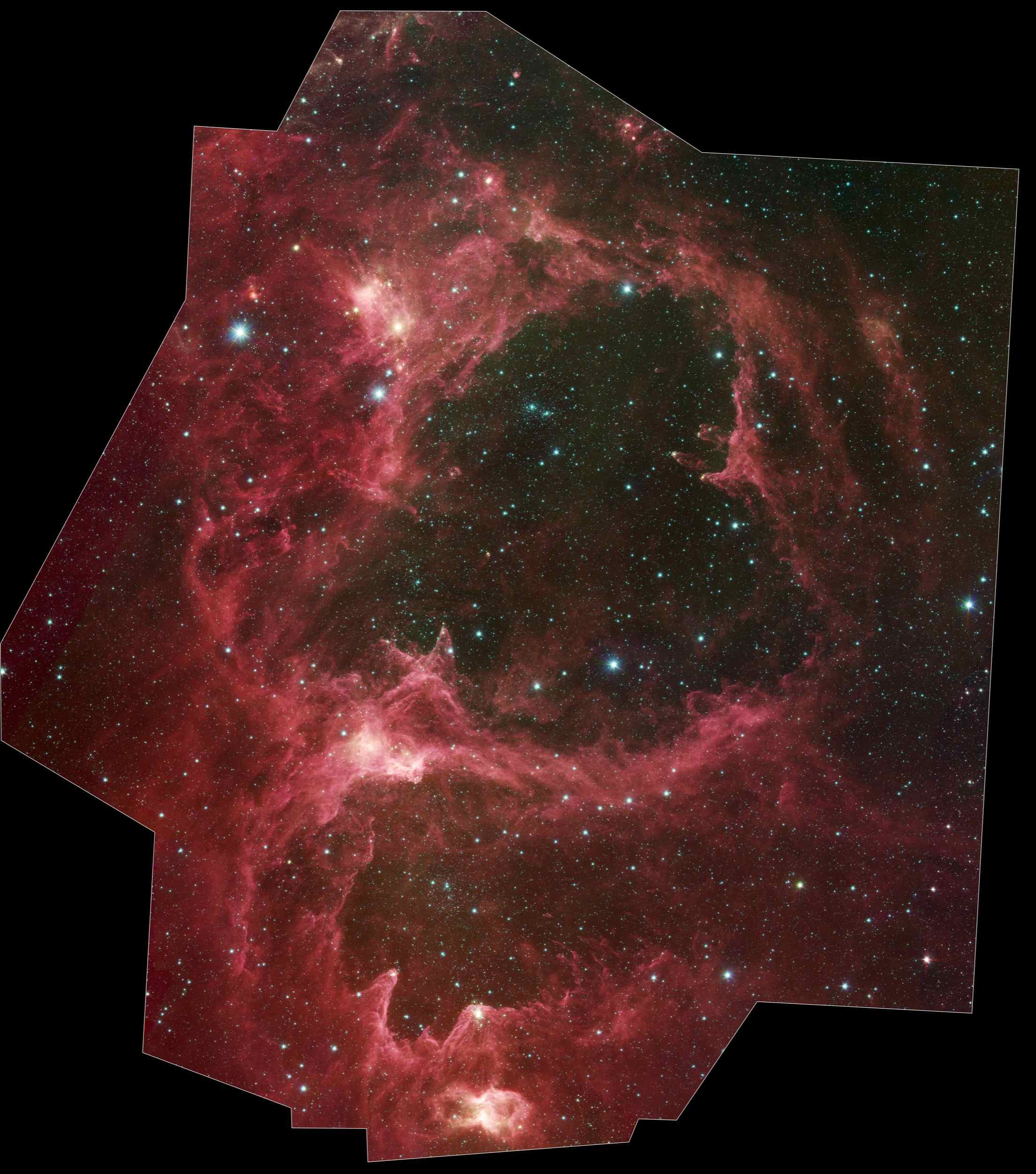 Generations of stars can be seen in this new infrared portrait from NASA's Spitzer Space Telescope. In this wispy star-forming region, called W5, the oldest stars can be seen as blue dots in the centers of the two hollow cavities.