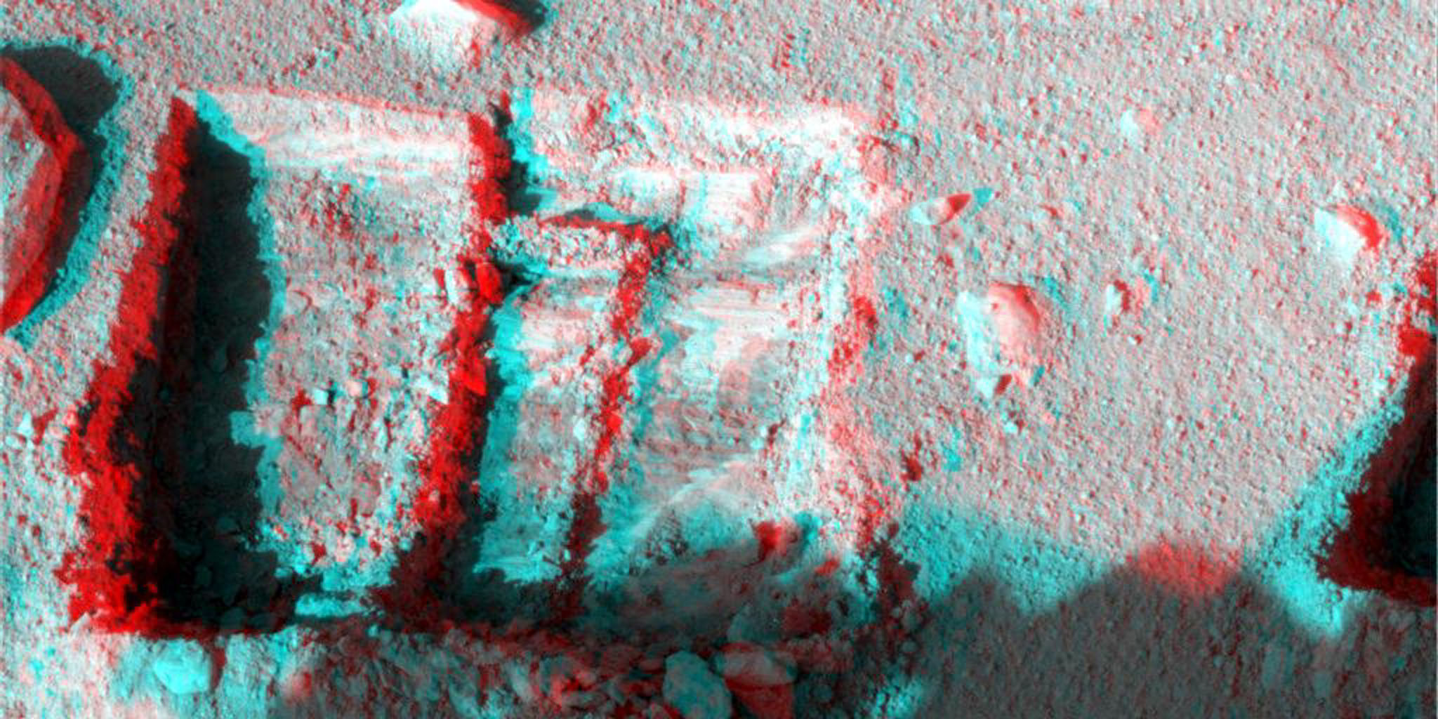 This anaglyph was taken by NASA's Phoenix Mars Lander's Surface Stereo Imager Oct. 7, 2008. The anaglyph highlights the depth of the trench, informally named 'La Mancha,' and reveals the ice layer beneath the soil surface. 3-D glasses are necessary.