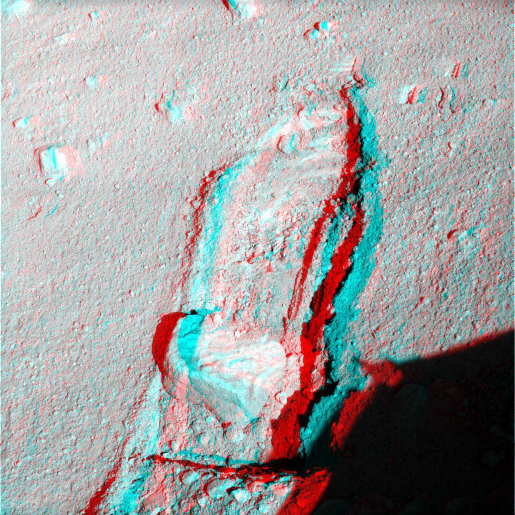 The robotic arm on NASA's Phoenix Mars Lander slid a rock out of the way on Sept. 22, 2008 to gain access to soil that had been underneath the rock. 3D glasses are necessary to view this image.