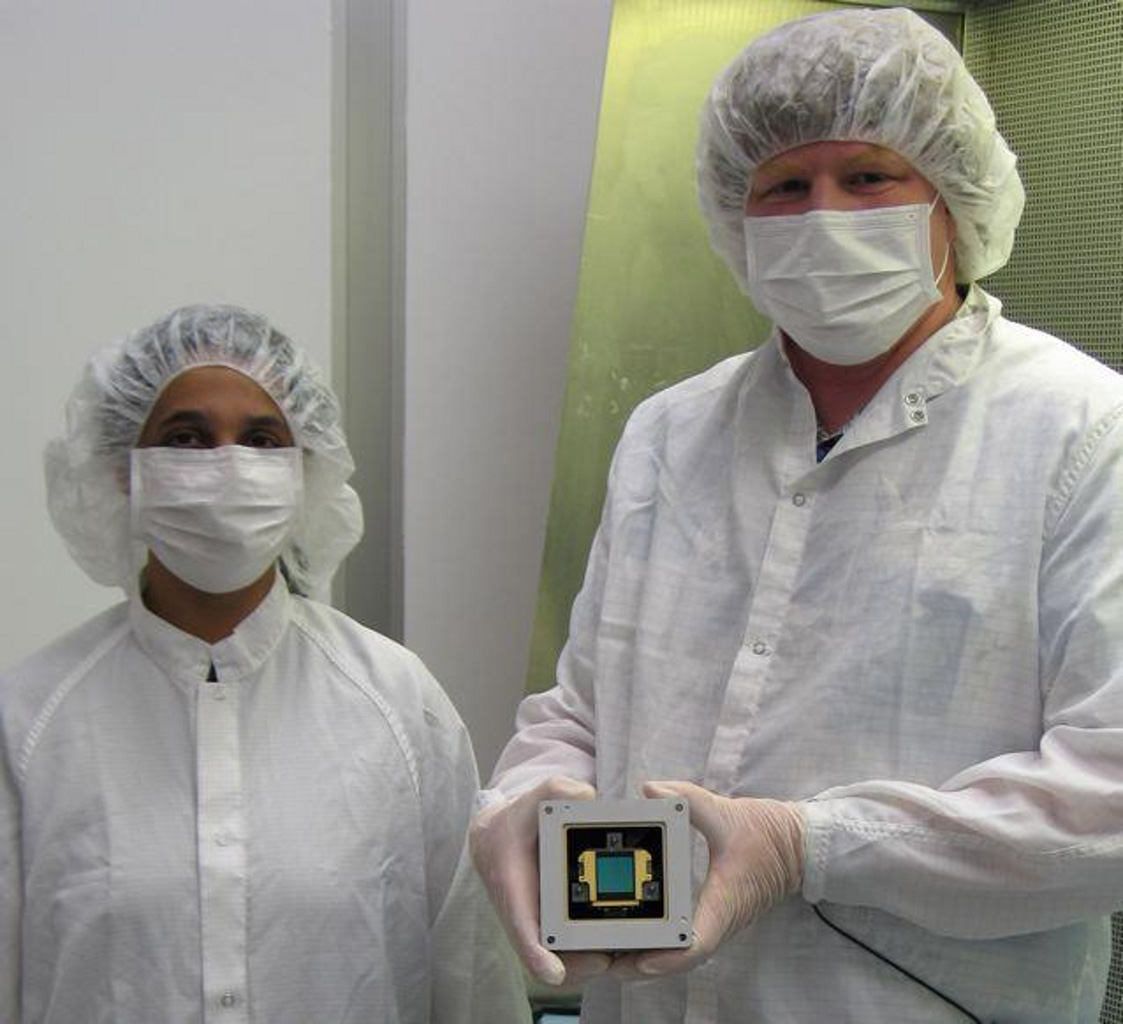 Mike Ressler (right) and Kalyani Sukhatme of NASA's JPL pose in the clean room with a model component, called a focal plane module, of the Mid-Infrared Instrument on NASA's James Webb Space Telescope.