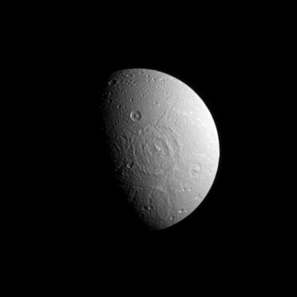 A broad impact basin hints at Dione's split personality in this image from NASA's Cassini spacecraft. Dione's leading hemisphere is heavily cratered by impacts while its trailing hemisphere features bright ice cliffs created by tectonic fractures.