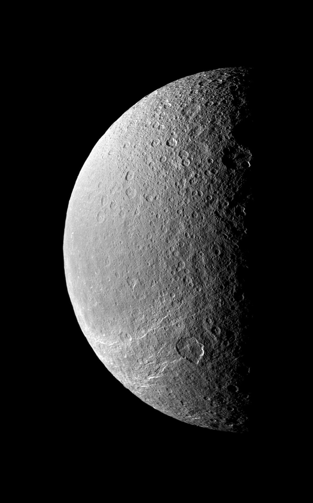 The terminator between light and dark throws Rhea's cratered surface into stark relief while the southern hemisphere is scored by bright icy cliffs. This image was taken in visible light with NASA's Cassini spacecraft's narrow-angle camera.