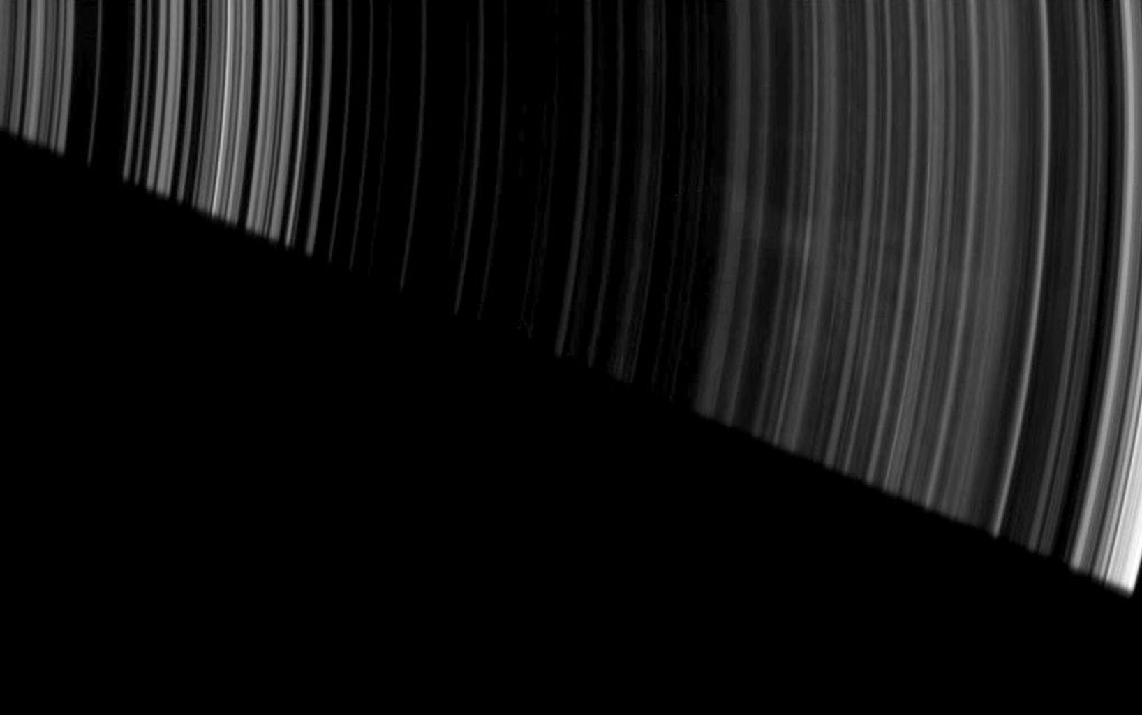 Faint, ghostly spokes dapple the dark side of Saturn's A ring as the planet's shadow makes a sharp diagonal cut across this image from NASA's Cassini spacecraft.