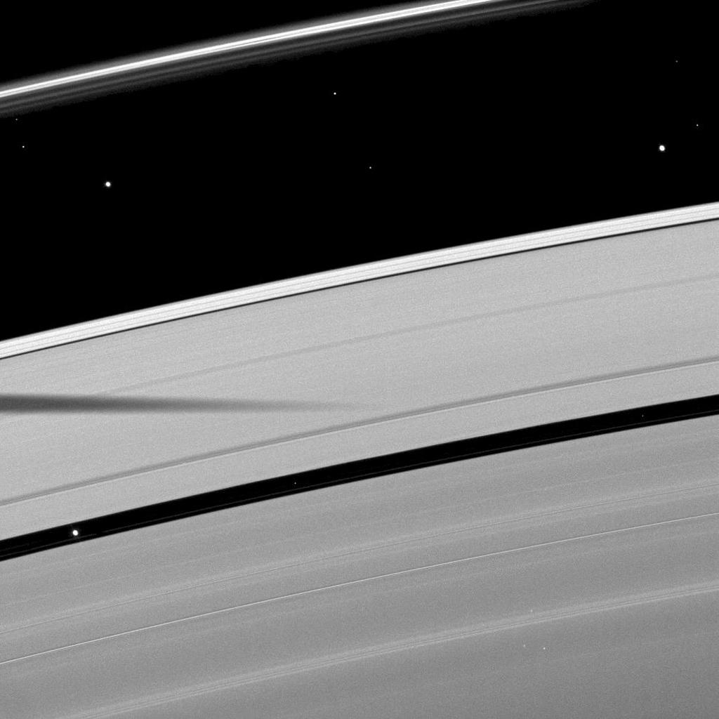The shadow of the moon Mimas is cast on Saturn's outer A ring in this image which also shows a couple of moons and a collection of stars.