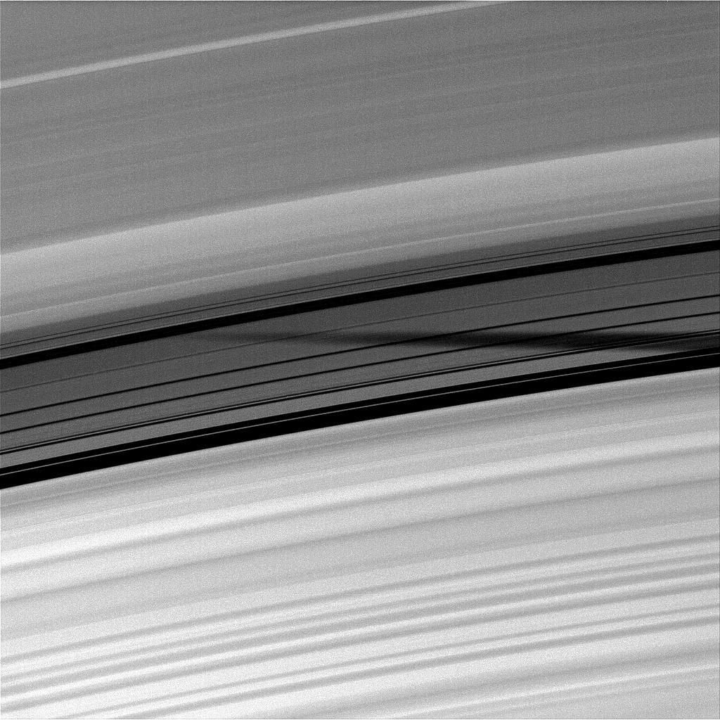 The shadow of the moon Mimas is seen through the unlit side of the Cassini Division of Saturn's rings.
