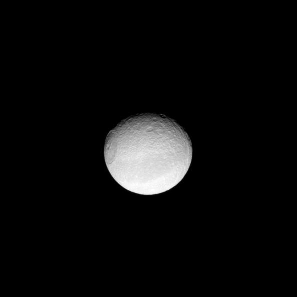 Appearing like an iris of a human eye, the huge Odysseus Crater dominates the sphere of Saturn's moon Tethys as seen by NASA's Cassini spacecraft.