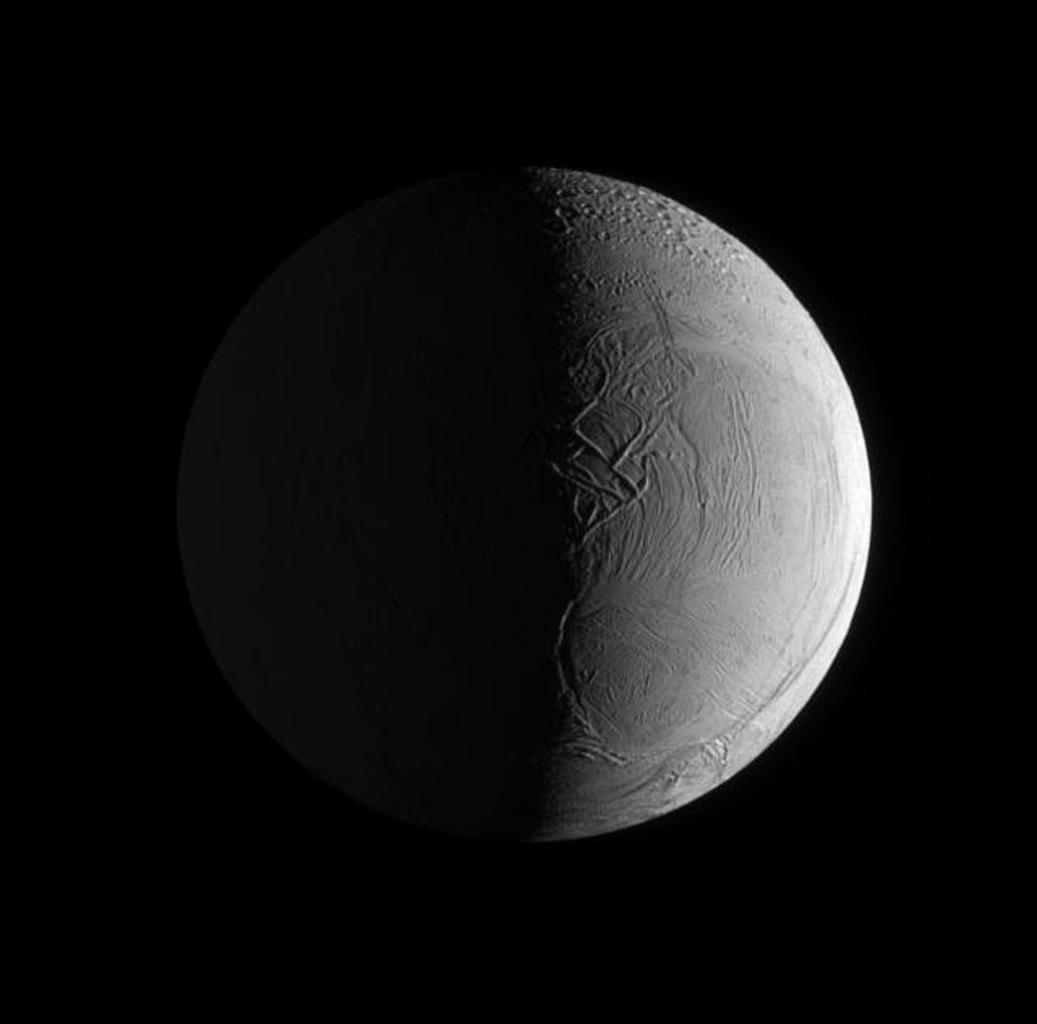 Two sources of light illuminate the textured surface of the moon Enceladus in this image taken by NASA's Cassini spacecraft's narrow angle camera.
