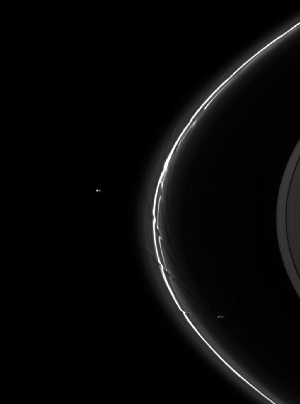 This image shows a pair of moons, Pandora and Prometheus, continuing their shepherding duties near Saturn's thin F ring as seen by NASA's Cassini spacecraft.