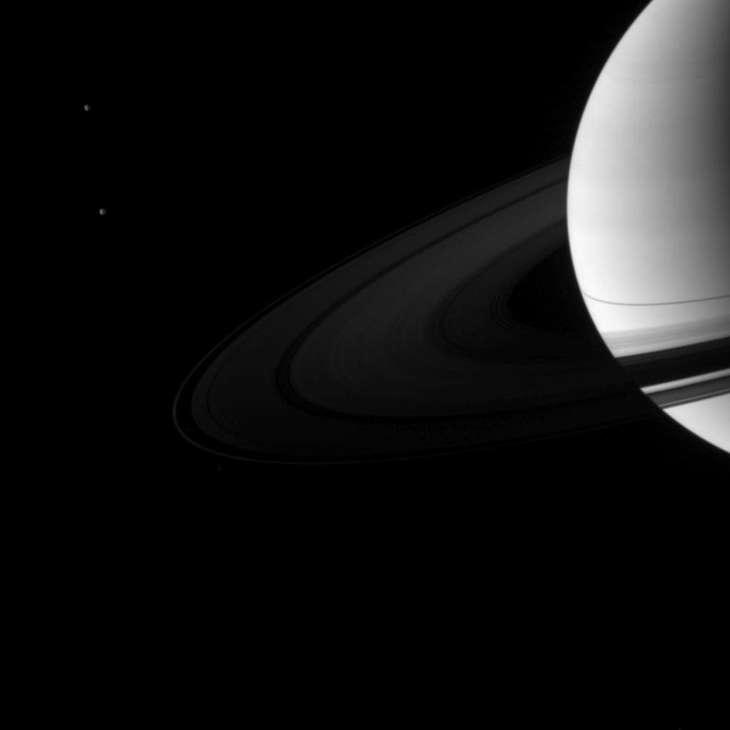 A pair of Saturn's moons, Dione and Tethys, accompany the planet and its rings in this image taken shortly after the planet's August 2009 equinox by NASA's Cassini spacecraft.