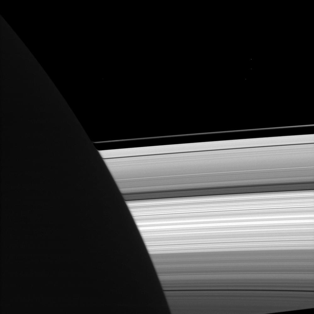 NASA's Cassini spacecraft looks past the night side of Saturn, dimly lit on the left of this image by ringshine, for a subtly distorted view of the planet's rings.