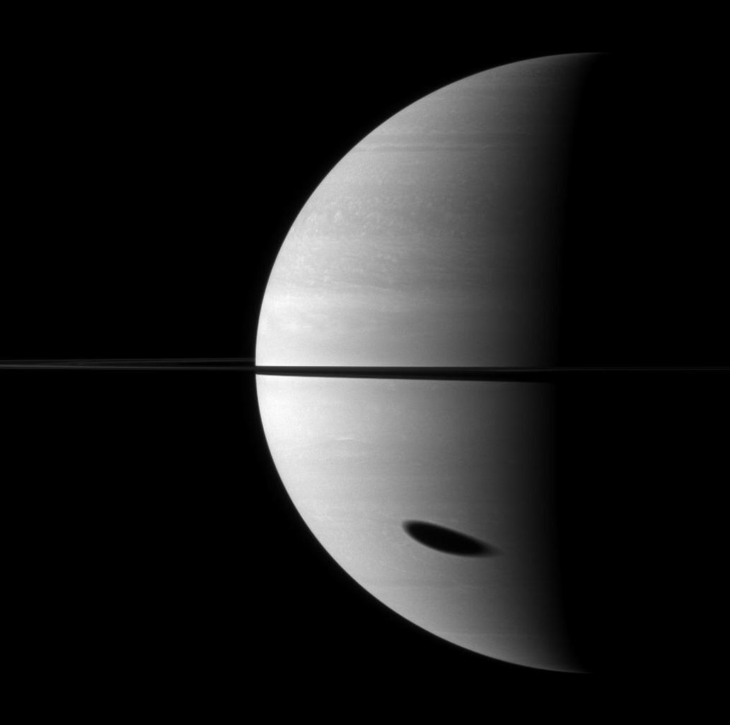 The shadow of Saturn's largest moon darkens a huge portion of the gas giant planet. Titan is not pictured here, but its shadow is elongated in the bottom right of the image.