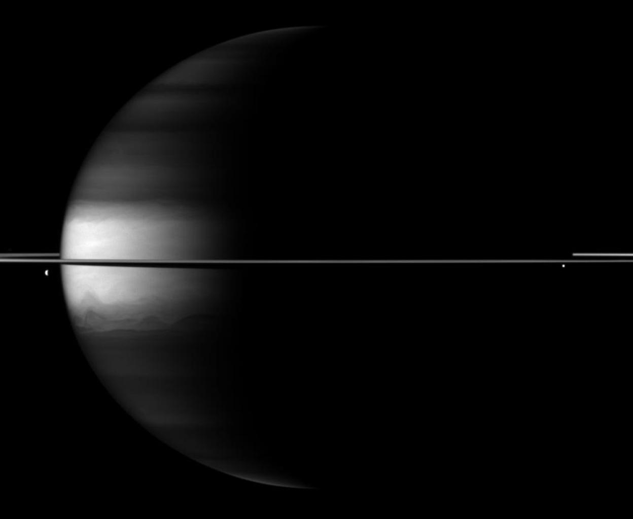 Dramatic differences between dark and light embellish image of Saturn, its rings and its moons Dione and Enceladus in this image taken by NASA's Cassini spacecraft.