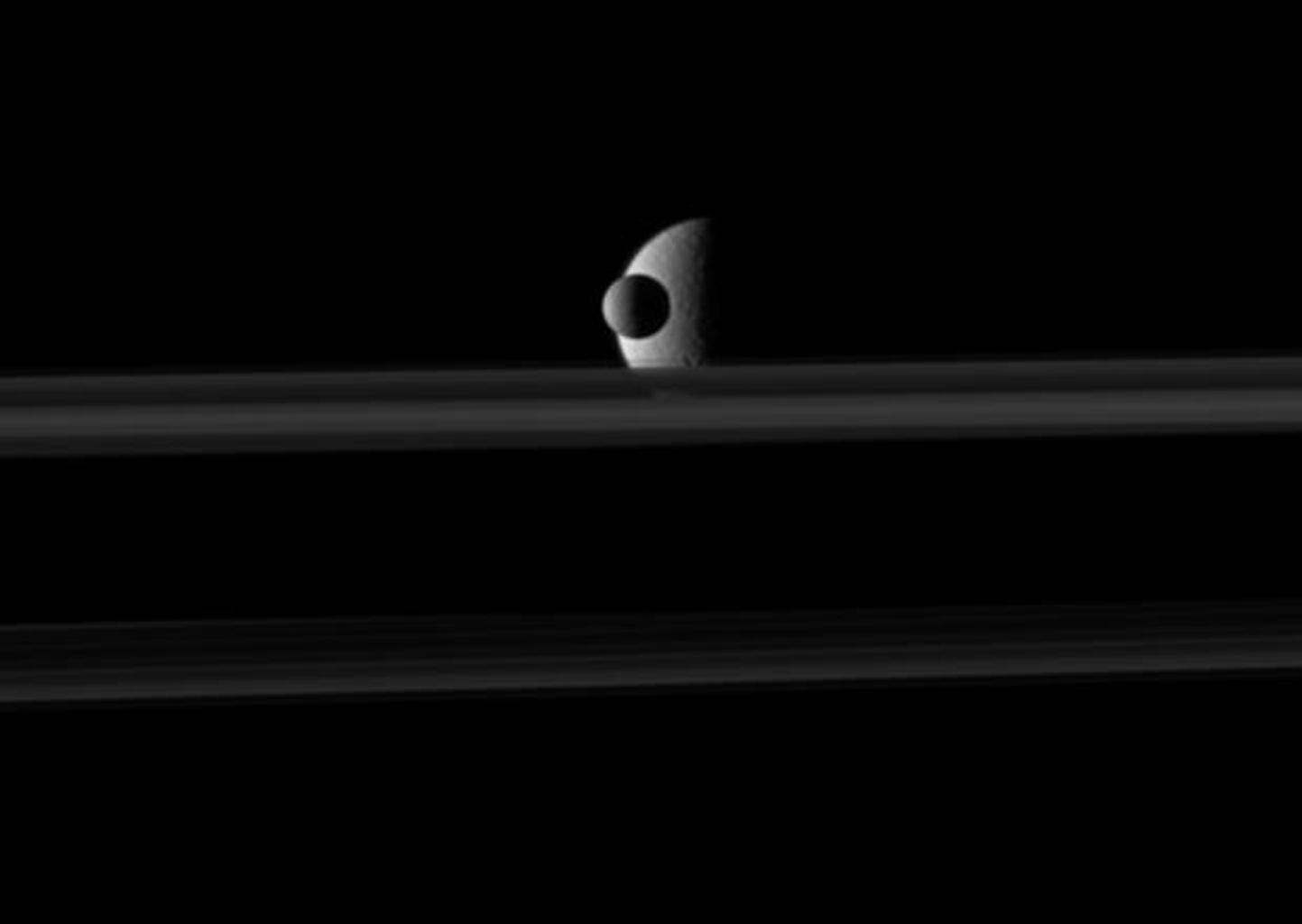 The small moon Mimas passes in front of the larger moon Rhea which is partly obscured by Saturn's rings in this image from NASA's Cassini spacecraft. Go to the Photojournal to view the animation.