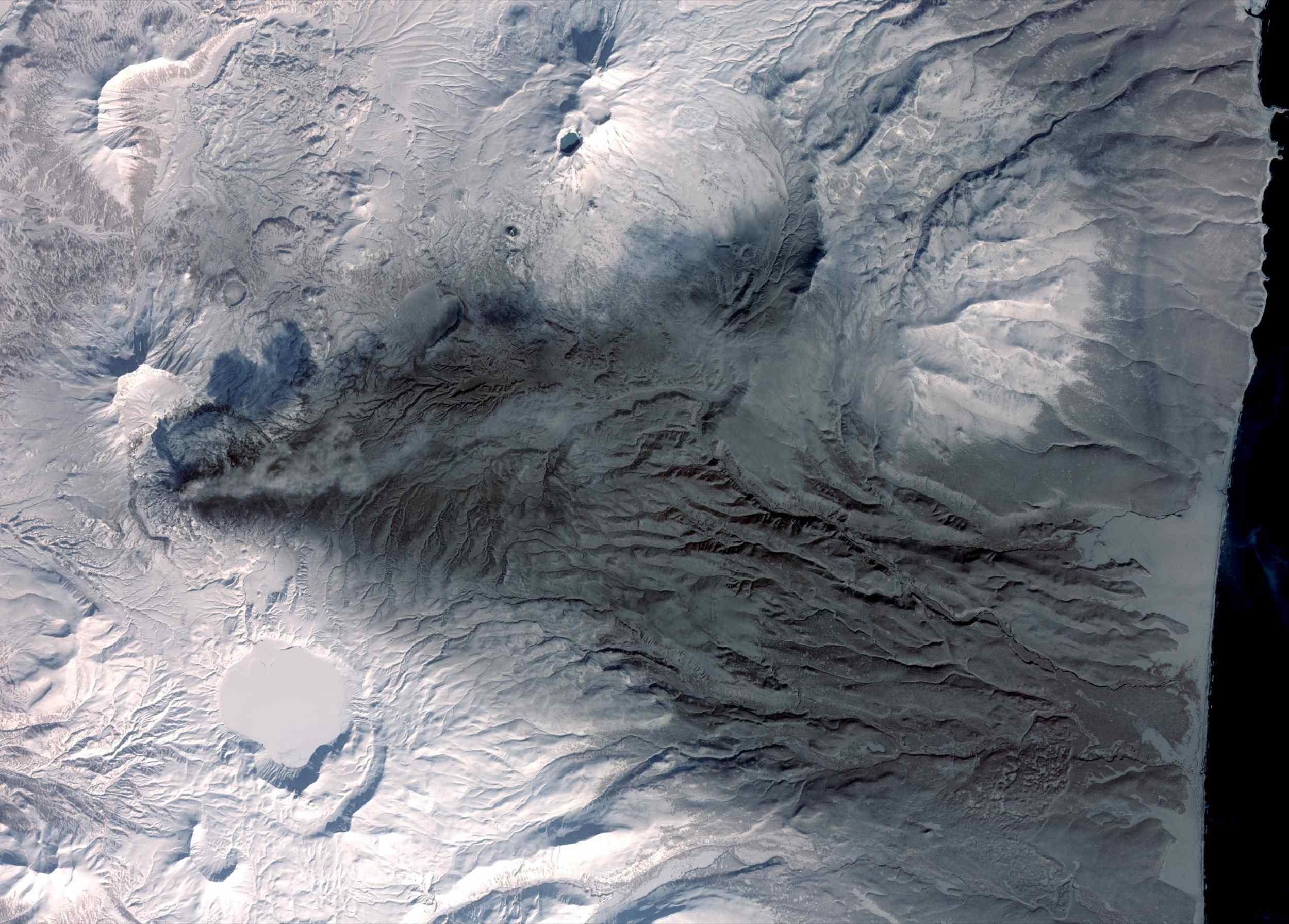 This image acquired by NASA's Terra spacecraft on March 6, 2009, shows early March eruptions of Karymsky volcano on Russia's Kamchatka Peninsula left the usually white snow a gray ashy color.