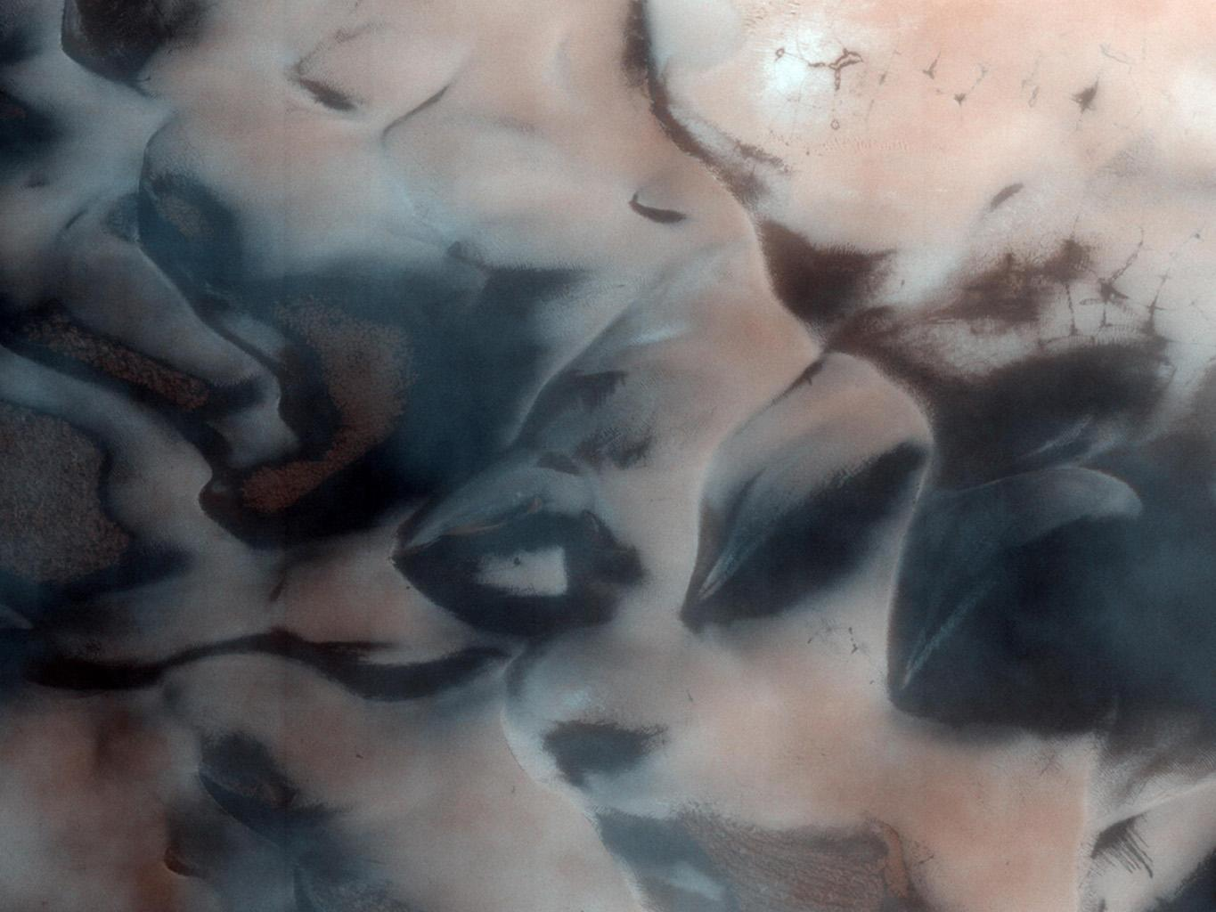 This image from NASA's Mars Reconnaissance Rover shows the north polar region of Mars is surrounded by a large sea of dark sand dunes that become covered by seasonal carbon dioxide frost.