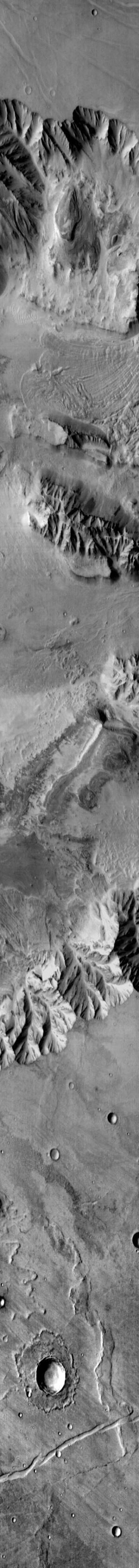 This image from NASA's Mars Odyssey shows Coprates Chasma, part of Valles Marineris on Mars. There is a large landslide deposit in the northern part of the chasma.