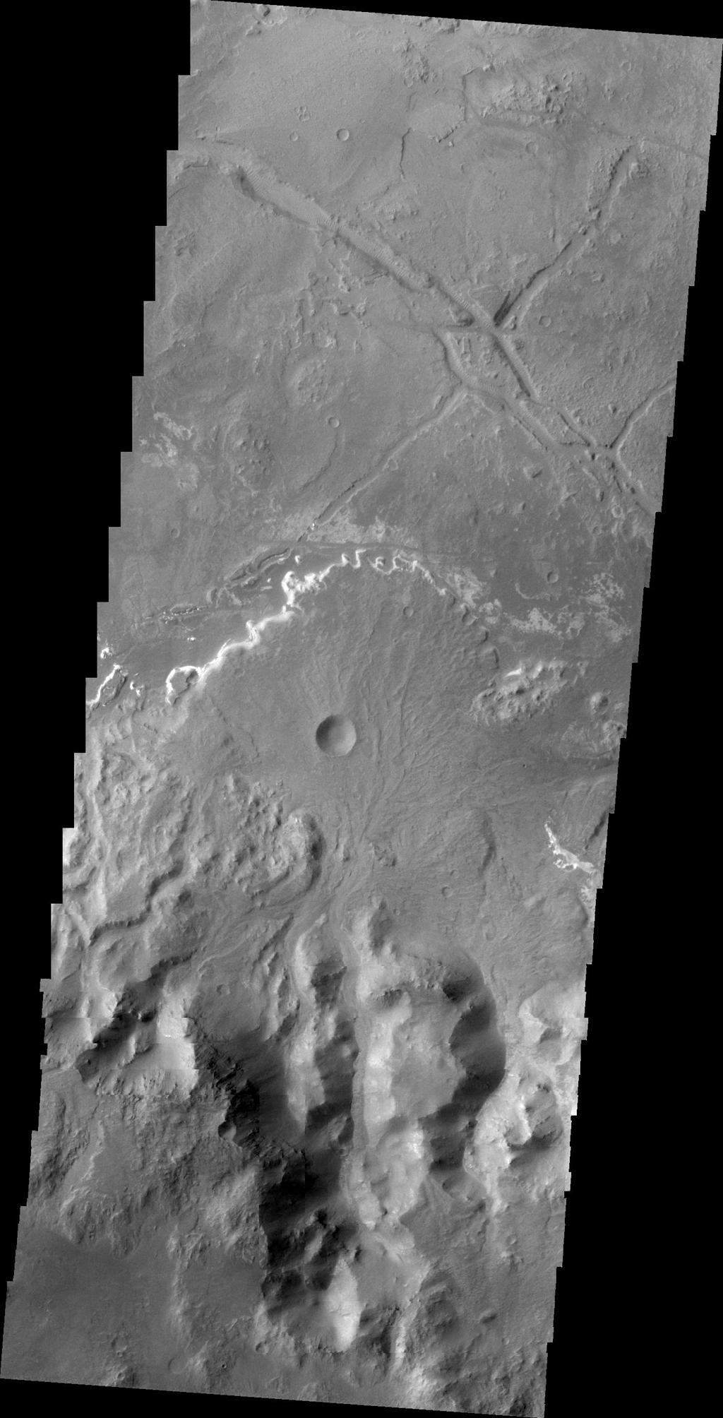This image from NASA's 2001 Mars Odyssey shows a delta deposit on the floor of Holden Crater. This delta was formed by small channels dissecting the rim of the crater, rather than the influx of material from Uzboi Vallis.