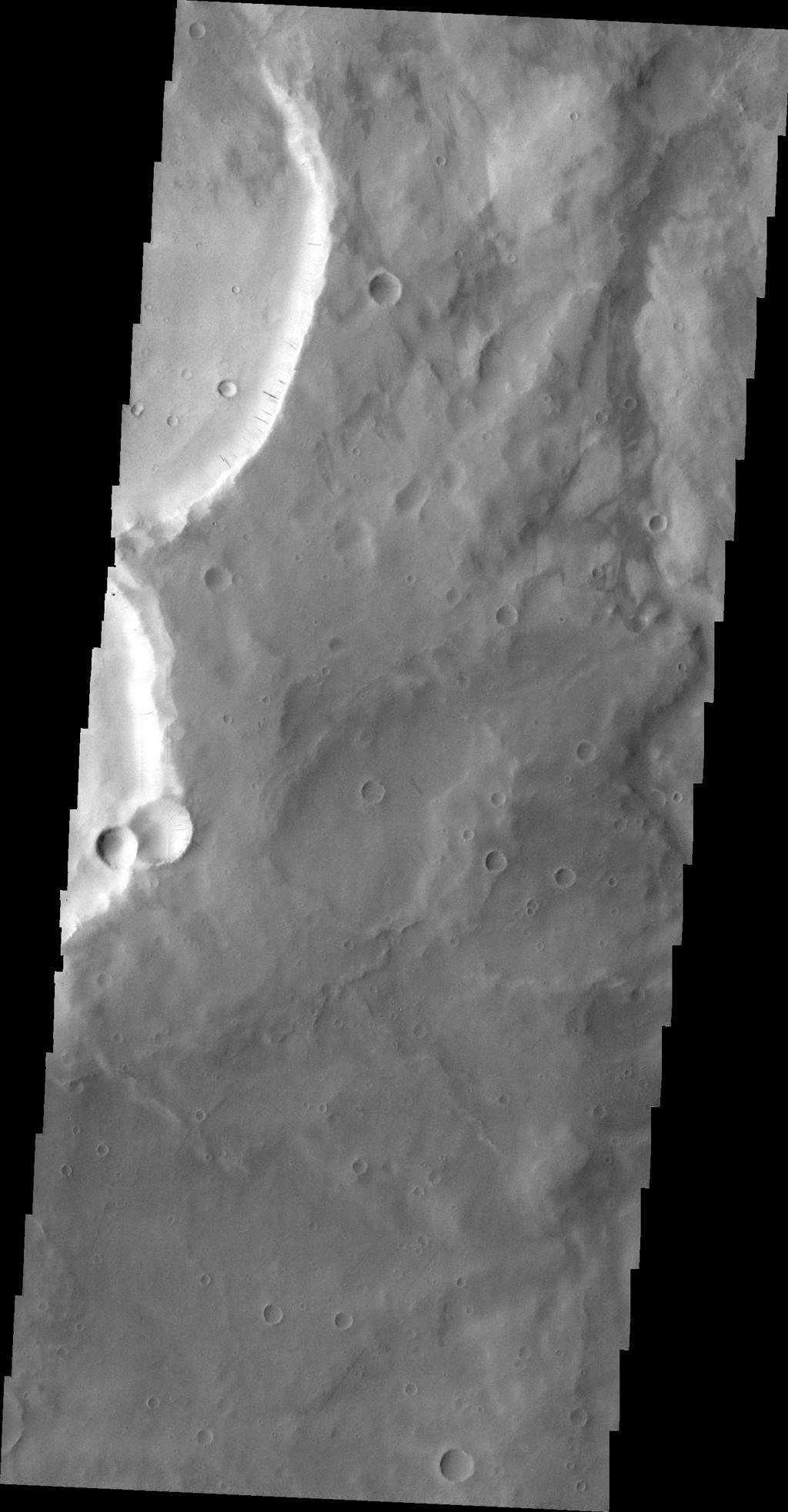 The dark slope streaks in this image are located on the rim of an unnamed crater east of Schiaparelli Crater taken by NASA's 2001 Mars Odyssey spacecraft.