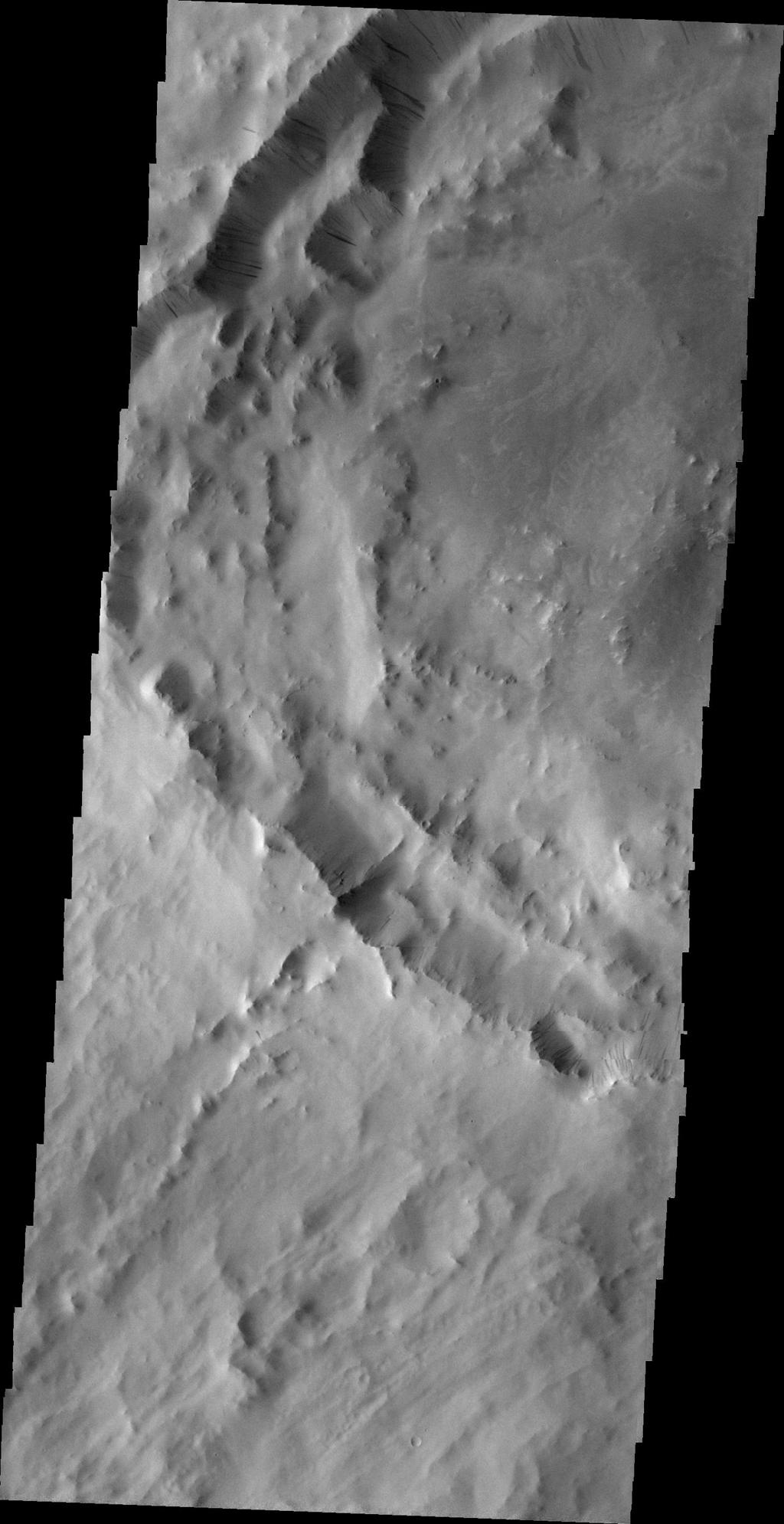 Numerous dark slope streaks mark the rim of this unnamed crater located on the rim of Henry Crater in this image taken by NASA's 2001 Mars Odyssey spacecraft.