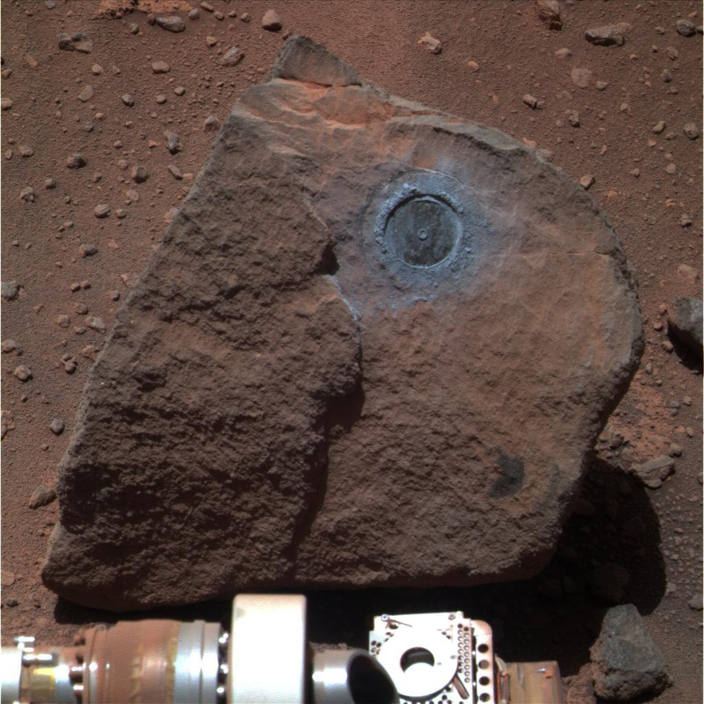 Perched on a rippled Martian plain, a dark rock not much bigger than a basketball was the target of interest for NASA's Opportunity during the past two months; Opportunity's rock abrasion tool brushed dust out of the circular area.