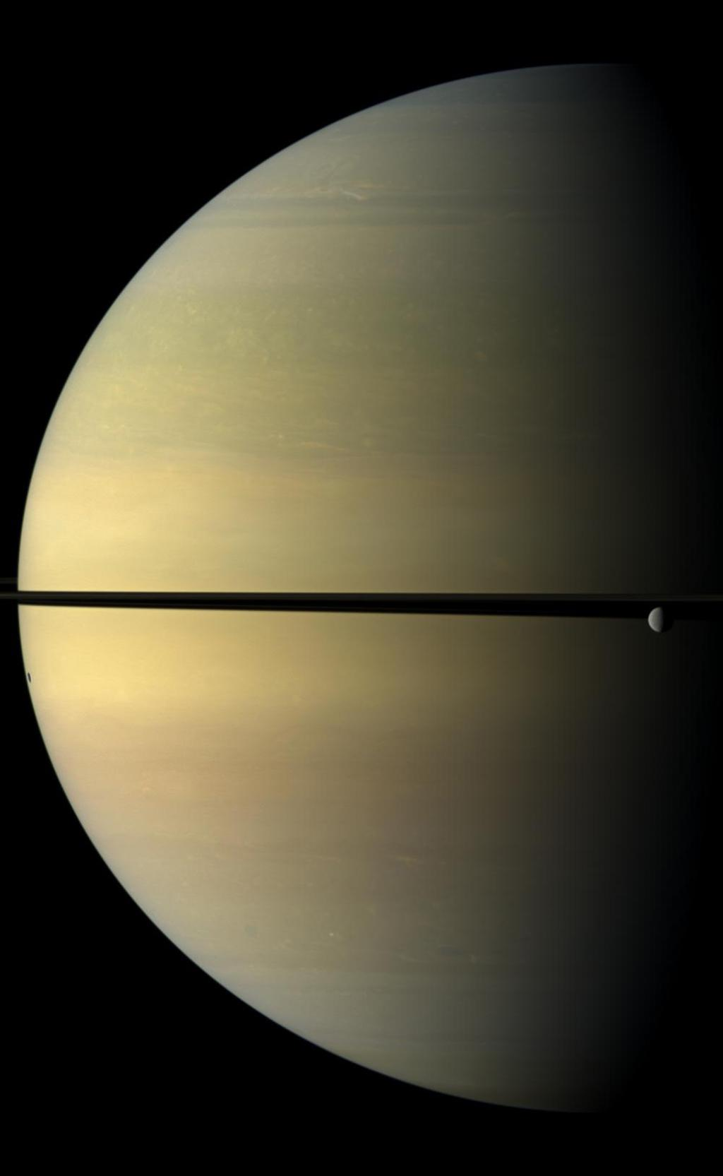 Saturn, stately and resplendent in this natural color view taken by NASA's Cassini spacecraft, dwarfs the icy moon Rhea. Rhea orbits beyond the rings on the right of the image. Tethys shadow is visible on the planet on the left of the image.