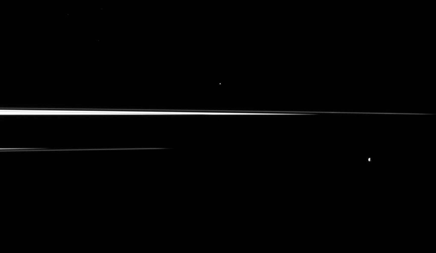 Saturn's shadow interrupts the planet's rings, leaving just thin slivers of the rings visible in this image, which shows a pair of the planet's small moons. Helene is in the center top of the image, Epimetheus is in the lower right.