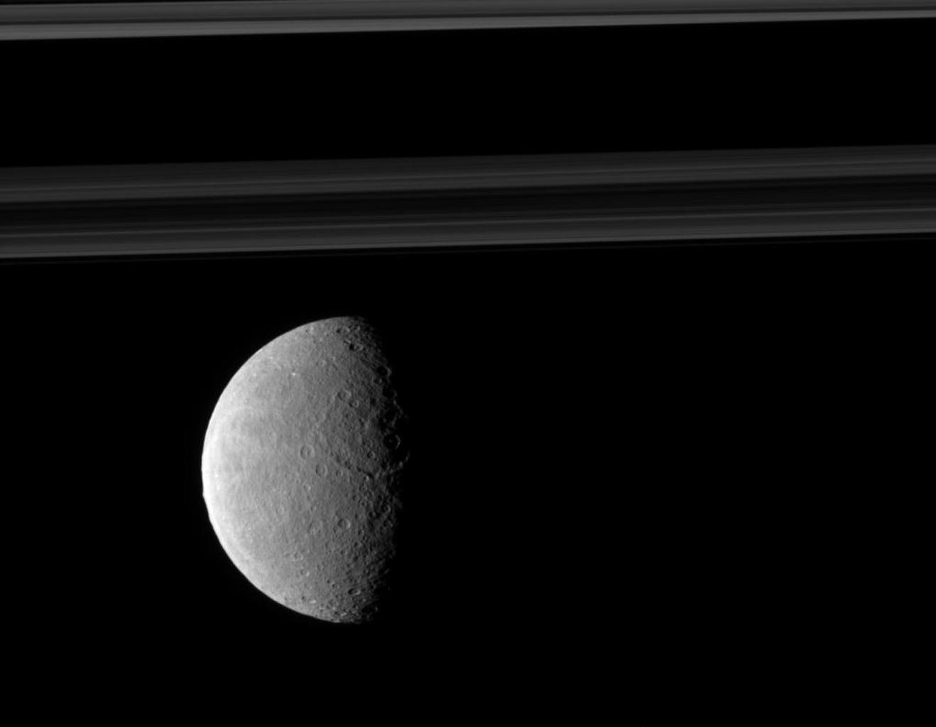 Rhea's trailing hemisphere shows off its wispy terrain on the left of this image taken by NASA's Cassini spacecraft which includes Saturn's rings in the distance.