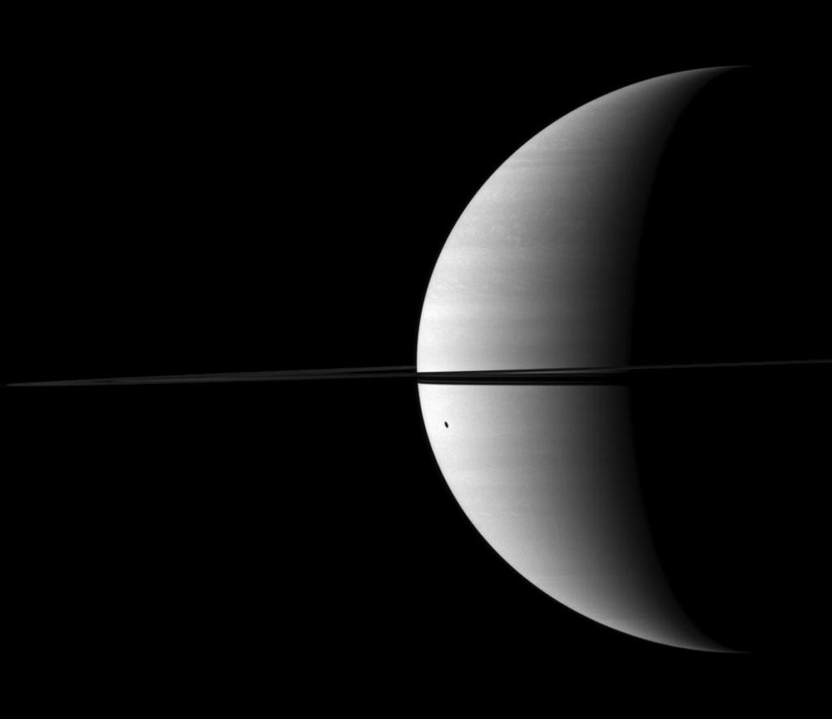 Dione's shadow is elongated as it is cast onto the round shape of Saturn in this image taken by NASA's Cassini spacecraft. The moon is not visible here. This view looks toward the northern, sunlit side of the rings from just above the ringplane.