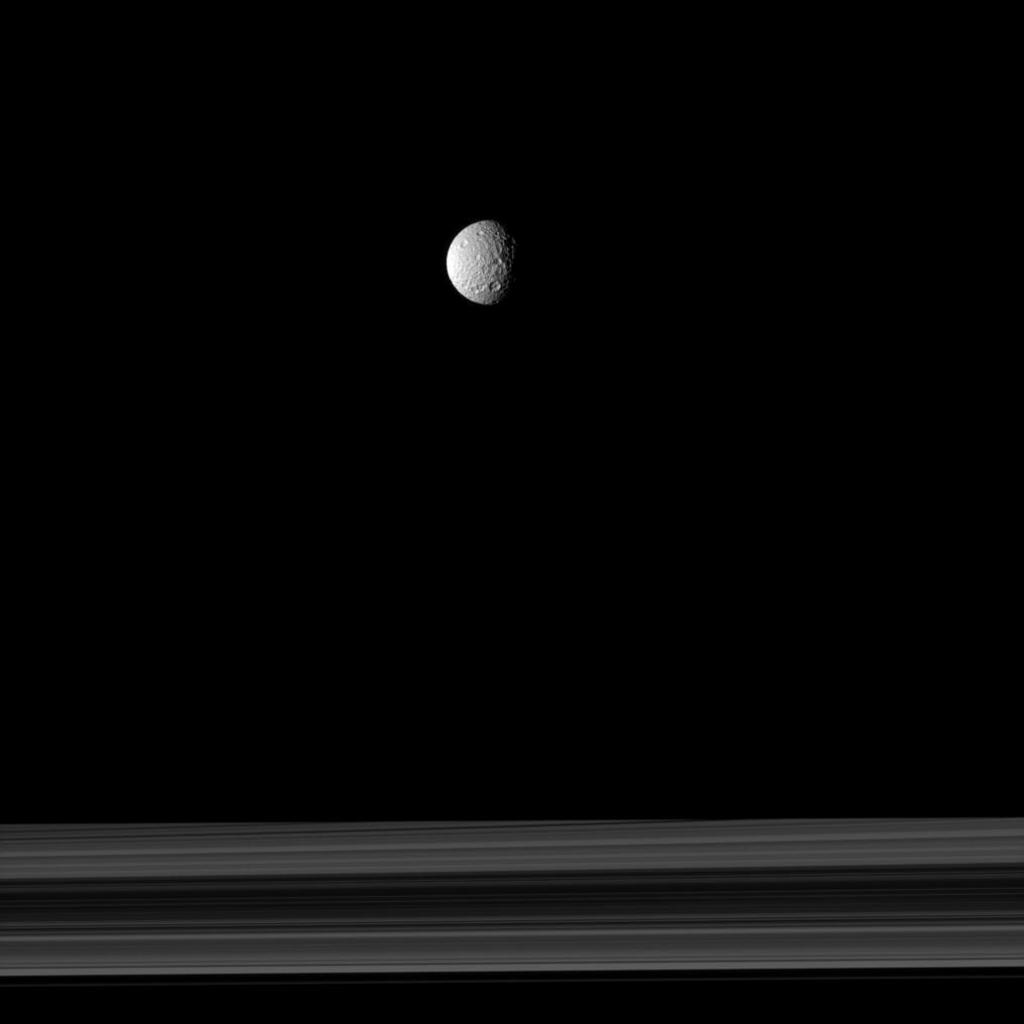 The cratered moon Mimas appears as if it has been hung like an ornament above Saturn's rings in this image taken by NASA's Cassini spacecraft.