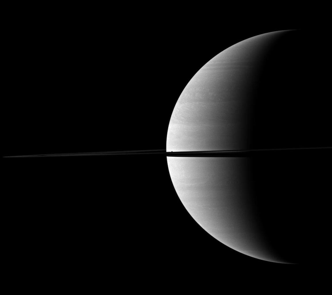 The diminutive moon Mimas can be found hiding in the middle of this view of a crescent of Saturn bisected by rings in this image captured by NASA's Cassini spacecraft. Mimas appears as a dark speck just about the ringplane near the center of the image. Th