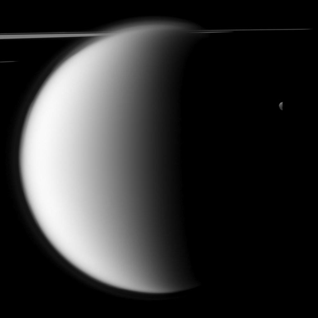 NASA's Cassini spacecraft captures a 'mutual event' between Titan and Mimas in front of a backdrop of the planet's rings. This image was snapped shortly before Saturn's largest moon passed in front of and occulted the small moon Mimas.