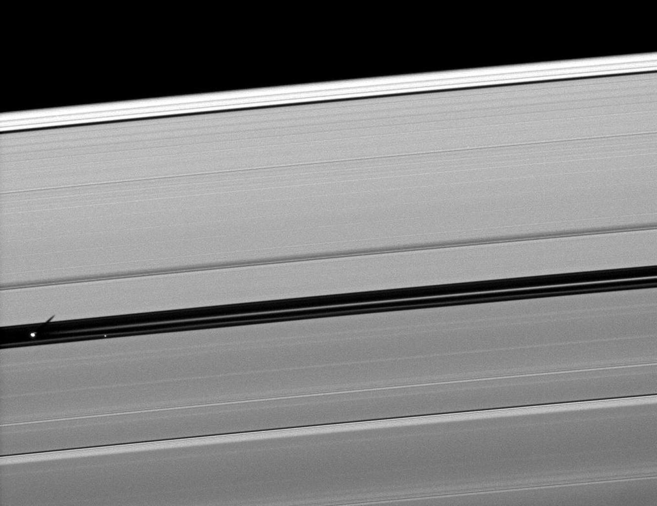 Orbiting in the Encke Gap of Saturn's A ring, the moon Pan casts a shadow on the ring in this image taken about six months after the planet's August 2009 equinox by NASA's Cassini spacecraft.