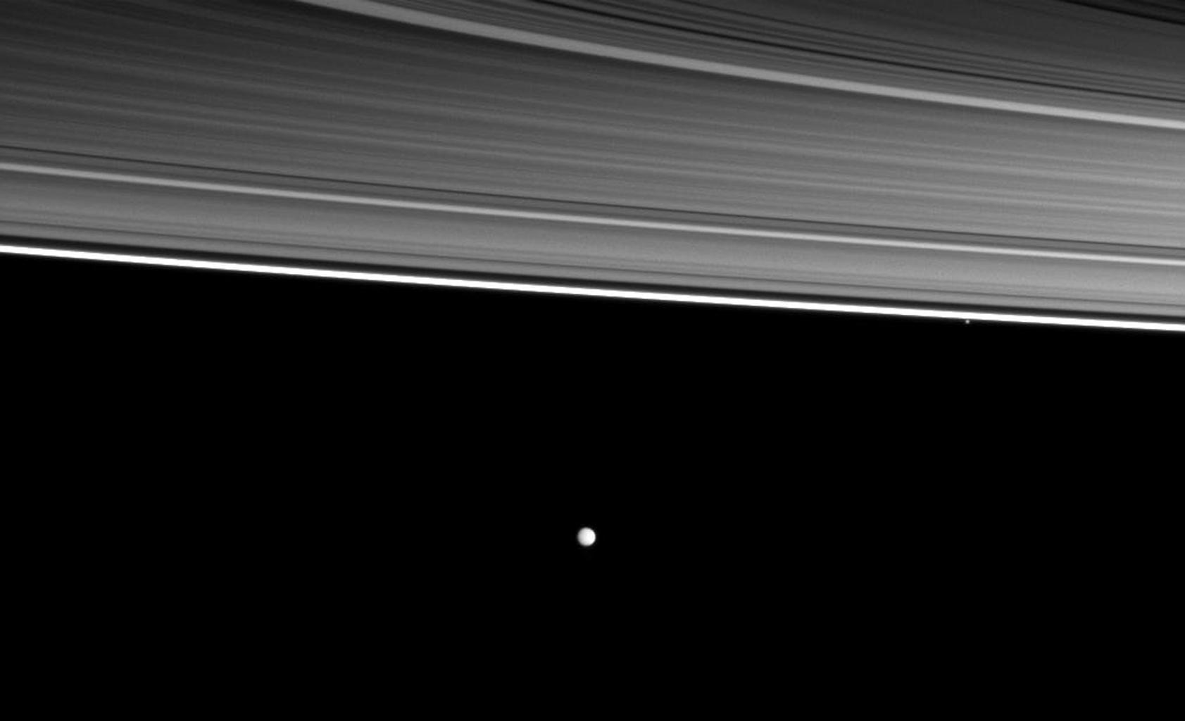 Two of Saturn's moons orbit beyond four of the planet's rings in this image from NASA's Cassini spacecraft. From the top right of the picture are the C, B, A, and thin F rings, the small moon Pandora and, near the middle of the image, the moon Enceladus.