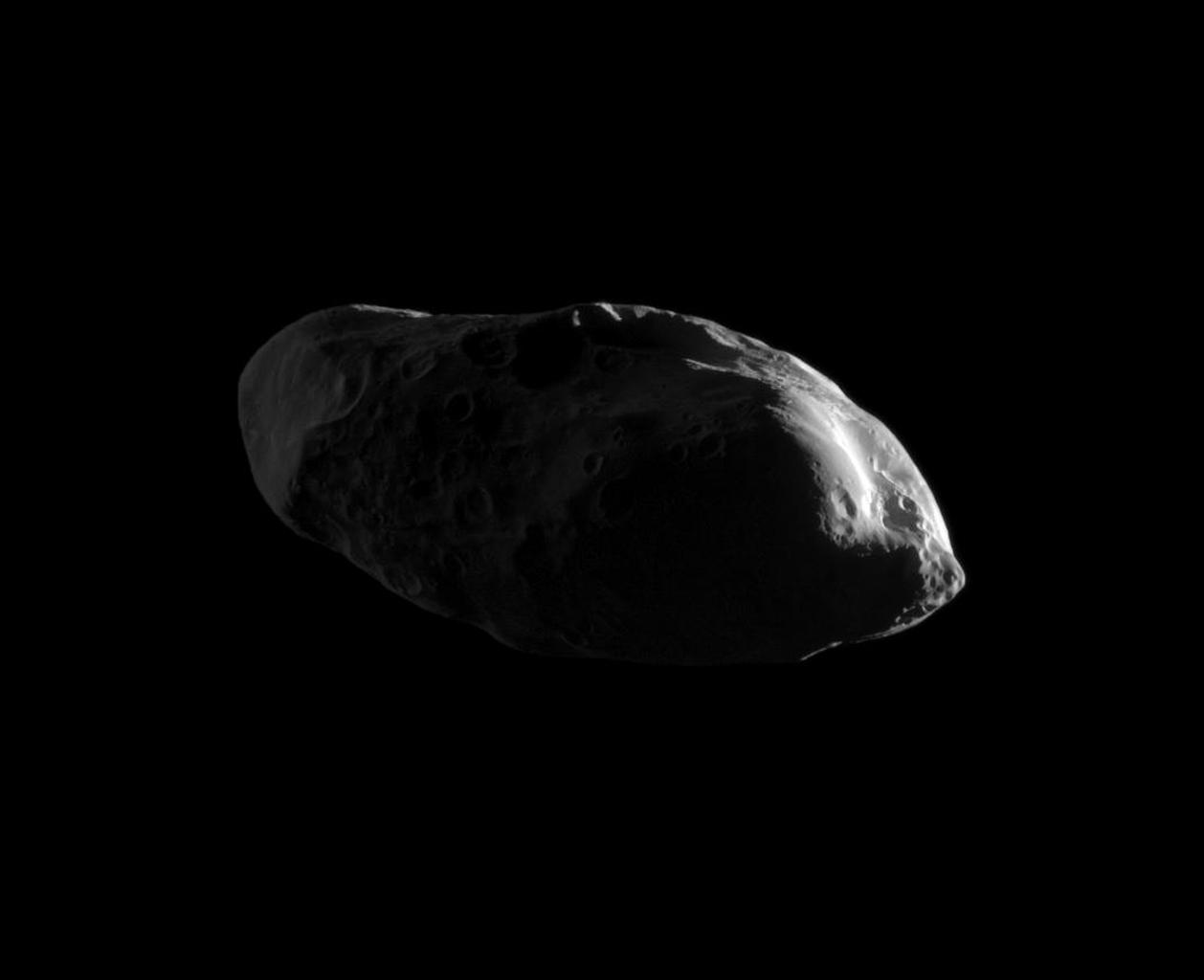 Appearing like eyes on a potato, craters cover the dimly lit surface of the moon Prometheus in this high-resolution image from NASA's Cassini spacecraft's early 2010 flyby.