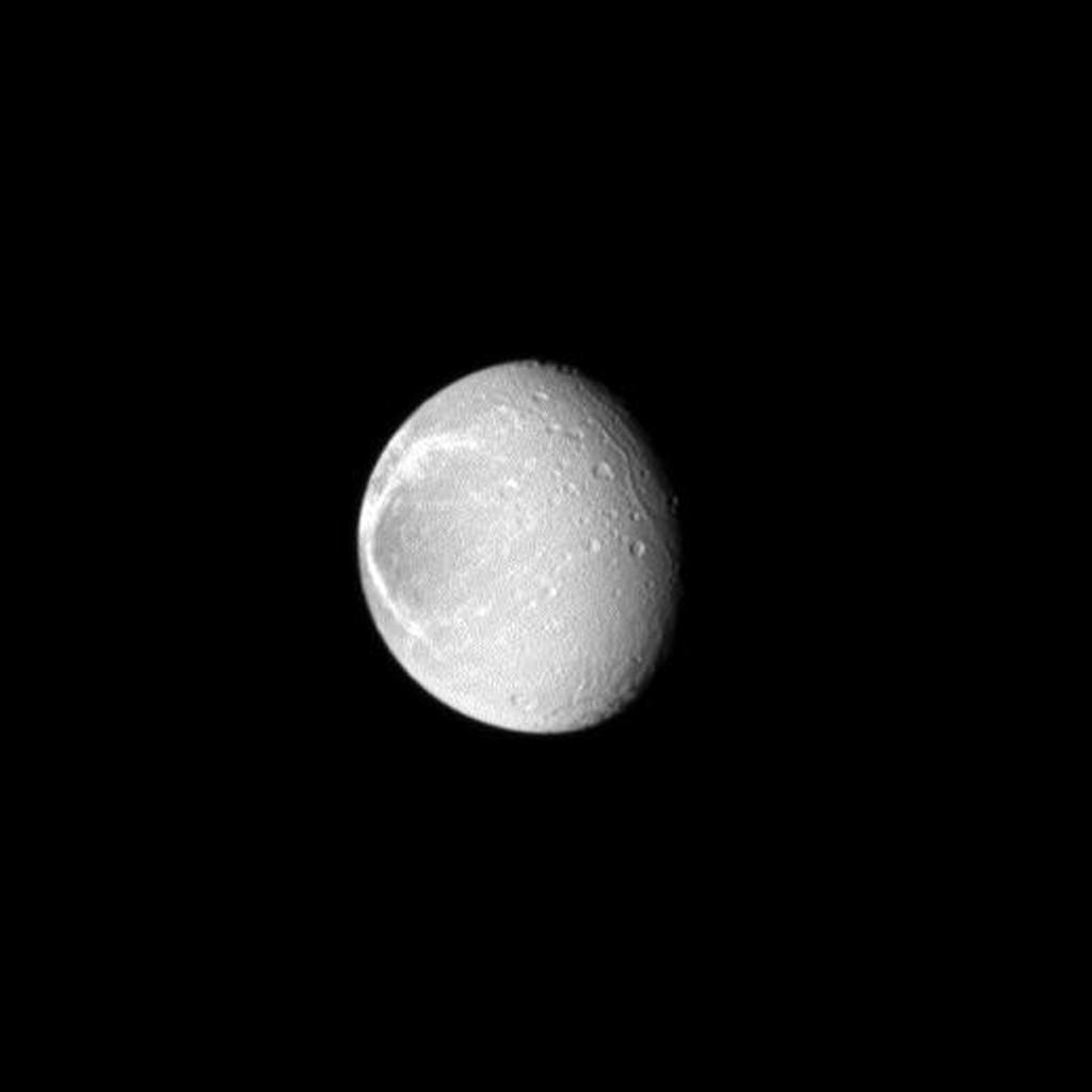 Sunlight highlights the bright, wispy features on the trailing hemisphere of Saturn's moon Dione as seen by NASA's Cassini spacecraft. These wispy features are a system of braided canyons with bright walls caused by fractures.