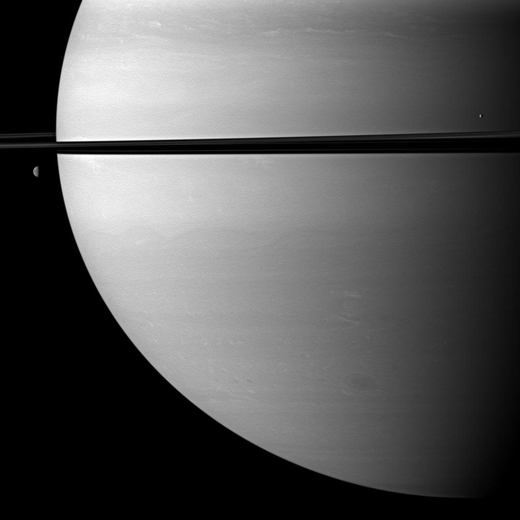Two moons orbit serenely before Saturn while large storms churn through the planet's southern hemisphere in this image taken by NASA's Cassini spacecraft. The moon Mimas is on the right. Dione is on the left.